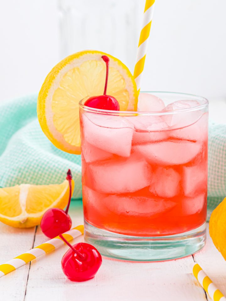 cherry cocktail with lemon and cherries on the table